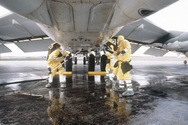 Members of the Strategic Air Command, wearing nuclear biological chemical (NBC) protective gear, scrub down a B-52H Stratofortress aircraft as they participate in a decontamination exercise during GLOBAL SHIELD '84