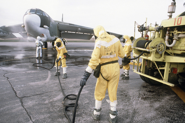 Members of the Strategic Air Command, wearing nuclear biological chemical (NBC) protective gear, prticipate in the decontamination of a B-52H Stratofortress aircraft during Exercise GLOBAL SHIELD '84