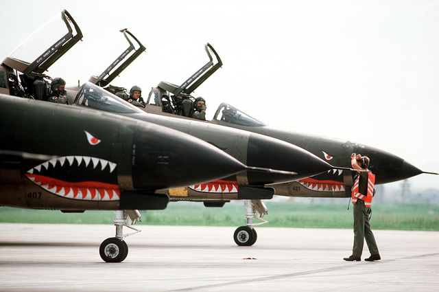 Pilots of the 51st Tactical Fighter Wing receive the go-ahead signal from a ground crewman prior to taxiing onto the runway for takeoff. AIRMAN Magazine, April 1984