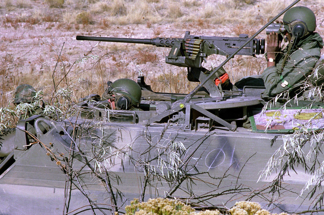 Soldiers in an M-113 armored personnel carrier participate in a downrange training exercise. An M-2 .50-cal. machine gun is mounted on the APC