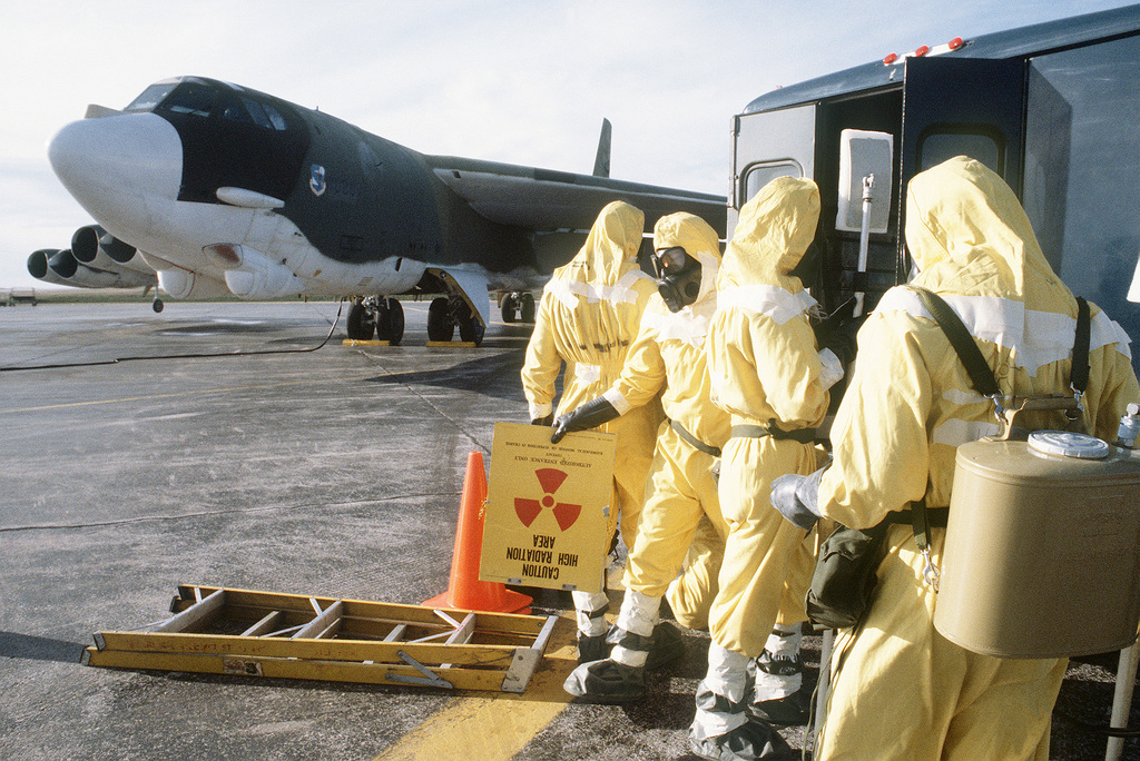 Strategic Air Command personnel, wearing nuclear biological chemical (NBC) protective gear, participate in a decontamination exercise during Exercise GLOBAL SHIELD '84. A B-52H Stratofortress aircraft is visible in the background