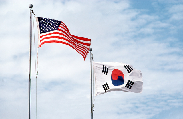 The US and Sough Korean flags fly side-by-side symbolizing the joint efforts of the two nations. AIRMAN Magazine, April 1984