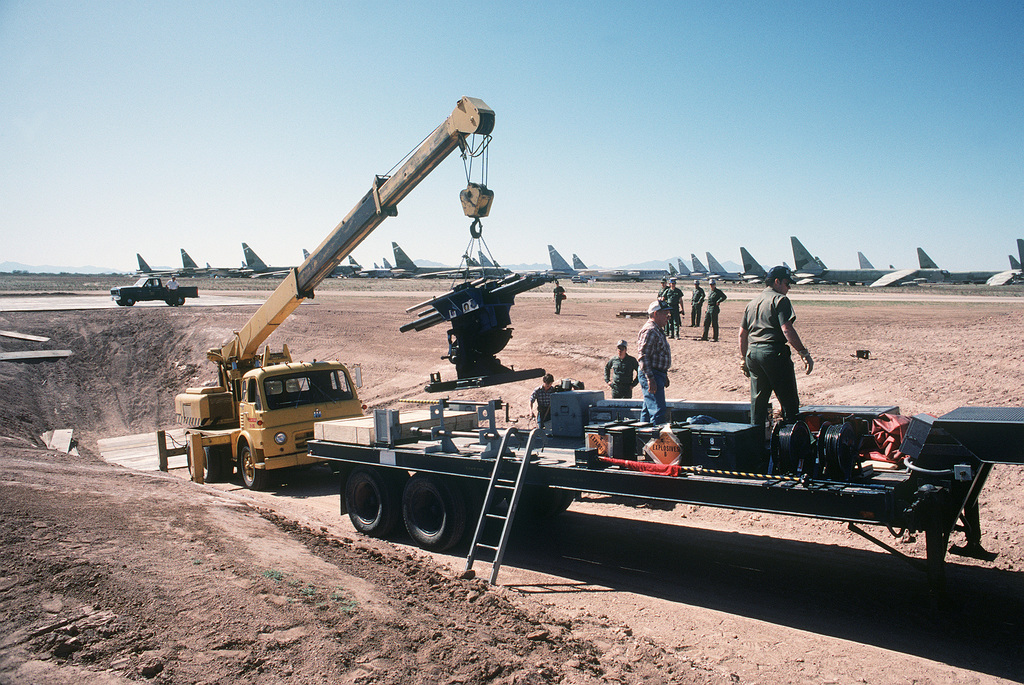 A crane lifts the battle damage infliction gun used to simulate anti-aircraft damage on aircraft during Exercise NIGHT/TRAIN/GLOBAL SHIELD '84. The gun was provided by the Foreign Munitions Test and Evaluation Group of the Air Force Wright Aeronautical Laboratories