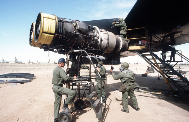 An inspector observes members of a combat logistics support squadron as the replace a damaged B-52 Stratofortress engine during Exercise NIGHT TRAIN/GLOBAL SHIELD '84. The crew is wearing nuclear, biological and chemical (NBC) gear