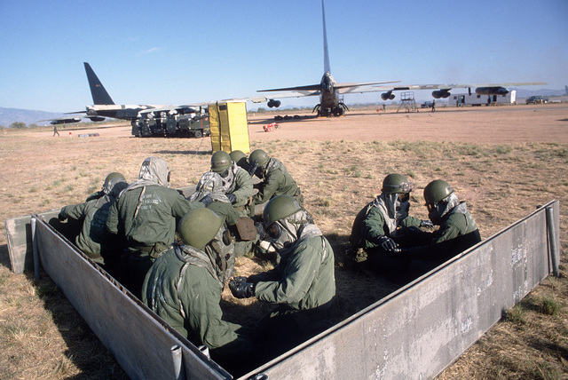 Members of a combat logistics support squadron wearing nuclear, biological and chemical (NBC) protective gear wait in a simulated shelter during a mock attack. They are repairing damaged B-52 Stratofortress aircraft during Exercise NIGHT TRAIN/GLOBAL SHIELD '84