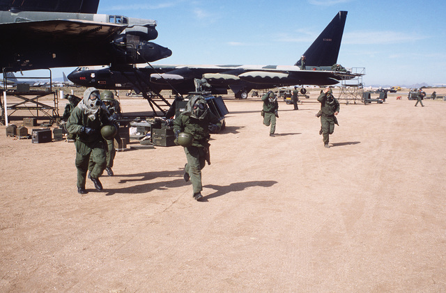 Members of a combat logistics support squadron wearing nuclear, biological and chemical (NBC) gear run to their assigned shelters during a mock attack. They are repairing damaged B-52 Stratofortress aircraft during Exercise NIGHT TRAIN/GLOBAL SHIELD '84