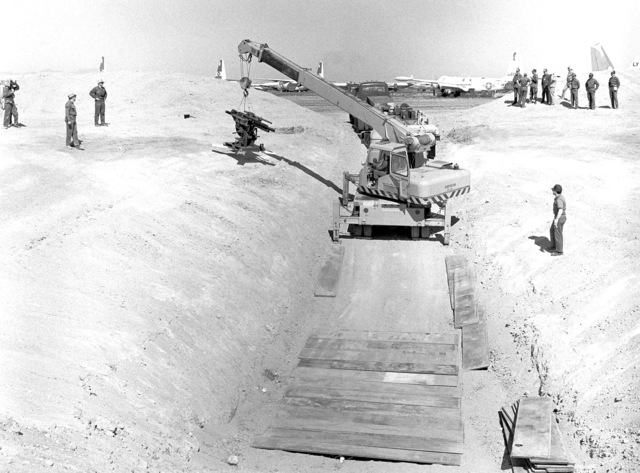 A crane is used to move a specially-designed cannon into a firing pit at the Military Aircraft Storage and Disposition Center (MASDC). Shrapnel damage inflicted by the cannon on an aircraft will be repaired by members of the 2954th Combat Logistics Support Squadron during the aircraft battle damage repair Exercise NIGHT TRAIN '84