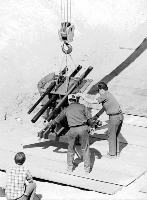 A specially-designed cannon is lowered into a firing pit at the Military Aircraft Storage and Disposition Center (MASDC). Shrapnel damage inflicted by the cannon on an aircraft will be repaired by members of the 2954th Combat Logistics Support Squadron during the aircraft battle damage repair Exercise NIGHT TRAIN '84
