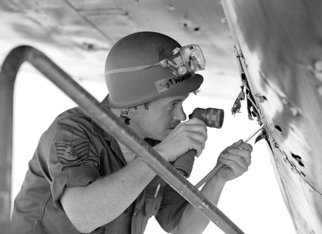 STAFF Sergeant Robert Winchester, a sheet metal technician with the 2954th Combat Logistics Support Squadron, uses a flashlight and a mirror to inspect damage on a B-52D Stratofortress aircraft during the aircraft battle damage Exercise NIGHT TRAIN '84. The damage caused by shrapnel fired from a specially-designed cannon