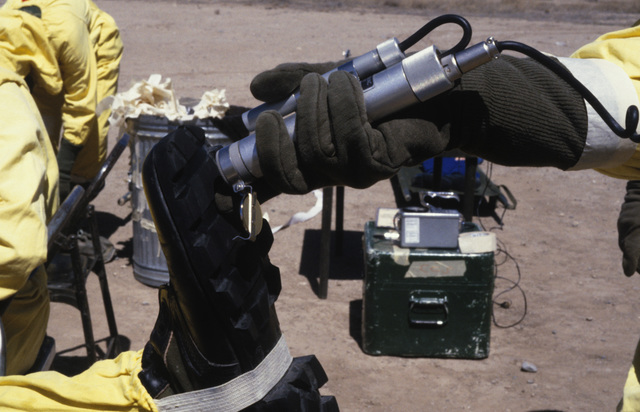 A contamination control station (CCS) team member uses a PDR-56 monitoring device to detect a possible contamination on another member's boot, during a Nuclear Emergency Team exercise at the Nuclear Weapons School