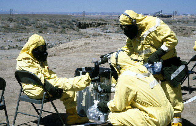 A contamination control station (CCS) team member uses PDR-56 monitoring device to detect possible contamination on another member's boot during a Nuclear Emergency Team exercise at the Nuclear Weapons School. They are wearing nuclear-biological-chemical (NBC) protective gear, and M-17 chemical-biological field masks
