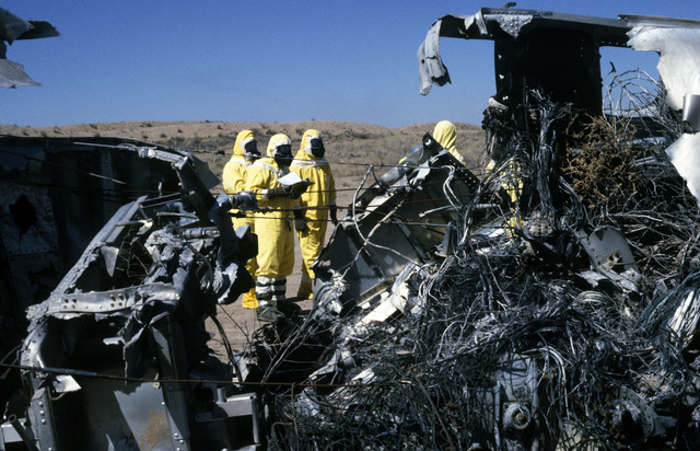An explosive ordnance disposal (EOD) team, wearing nuclear-biological-chemical (NBC) protective gear, surveys a simulated crash site during a Nuclear Emergency Team exercise at the Nuclear Weapons School