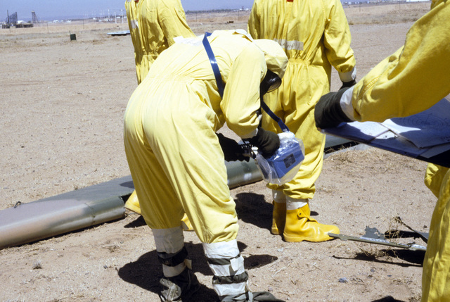 An explosive ordnance disposal team, wearing nuclear biological chemical (NBC) protective gear, use monitoring devices to detect contamination at a simulated crash site, during a Nuclear Emergency Team exercise at the Nuclear Weapons School