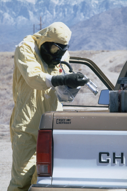 MASTER Sergeant (MSGT) James Holcomb, wearing nuclear-biological-chemical (NBC) protective gear, uses a PDR-56 monitoring device to detect possible contamination on a vehicle during a Nuclear Emergency Team exercise at the Nuclear Weapons School. He is also wearing an M-17 chemical-biological field mask