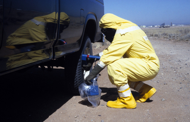 MASTER Sergeant (MSGT) James Holcomb, wearing nuclear-biological-chemical (NBC) protective gear, uses a PDR-56 monitoring device to detect possible contamination on a vehicle during a Nuclear Emergency Team exercise at the Nuclear Weapons School