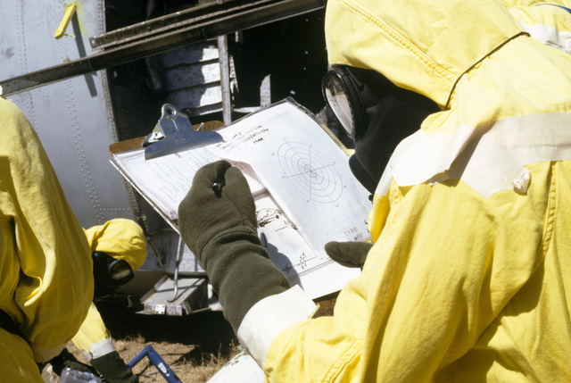 MASTER Sergeant (MSGT) James Kern, wearing nuclear biological chemical (NBC) protective gear, plots readings taken from detection equipment, as it monitors a simulated crash site for contamination. He is participating in a Nuclear Emergency Team exercise at the Nuclear Weapons School