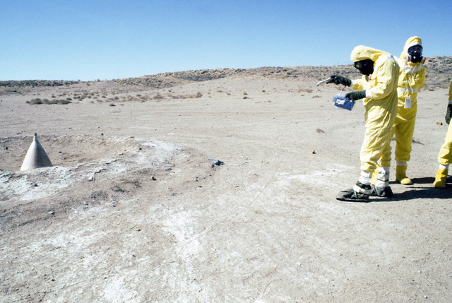 MASTER Sergeant (MSGT) John Bolinger, wearing nuclear biological chemical (NBC) protective gear, uses a PDR-27 monitoring device to detect gamma radiation contamination at a simulated crash site, during a Nuclear Emergency Team exercise at the Nuclear Weapons School