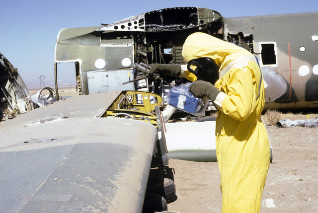 MASTER Sergeant (MSGT) John Tice, wearing nuclear biological chemical (NBC) protective gear, uses a PDR-27 monitoring device to detect possible contamination on an aircraft at a simulated crash site, during a Nuclear Emergency Team exercise at the Nuclear Weapons School