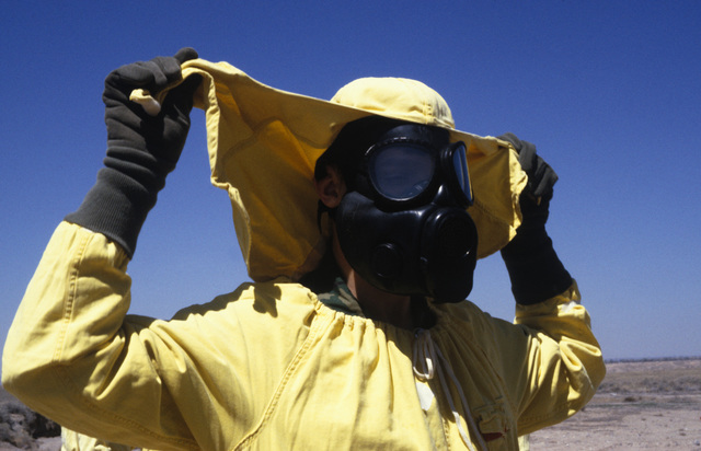 MASTER Sergeant (MSGT) Ronald Yurek removes the hood to his nuclear-biological-chemical (NBC) protective suit as he is processed through the contamination control station (CCS), during a Nuclear Emergency Team exercise at the Nuclear Weapons School. He is wearing an M-17 chemical-biological field mask