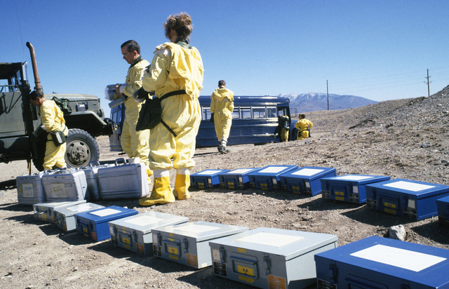 Members of an explosive ordnance disposal (EOD) team, wearing nuclear-biological-chemical (NBC) protective gear, organize instruments prior to conducting a decontamination exercise at the Nuclear Weapons School