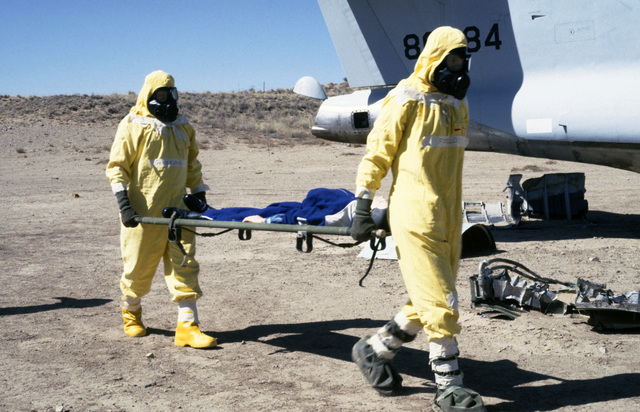Sergeant (SGT) Michael Field and Technical Sergent (TSGT) Jose Gonzalez, wearing nuclear-biological-chemical (NBC) protective gear, remove a casualty from a simulated crash site during a Nuclear Emergency Team exercise at the Nuclear Weapons School