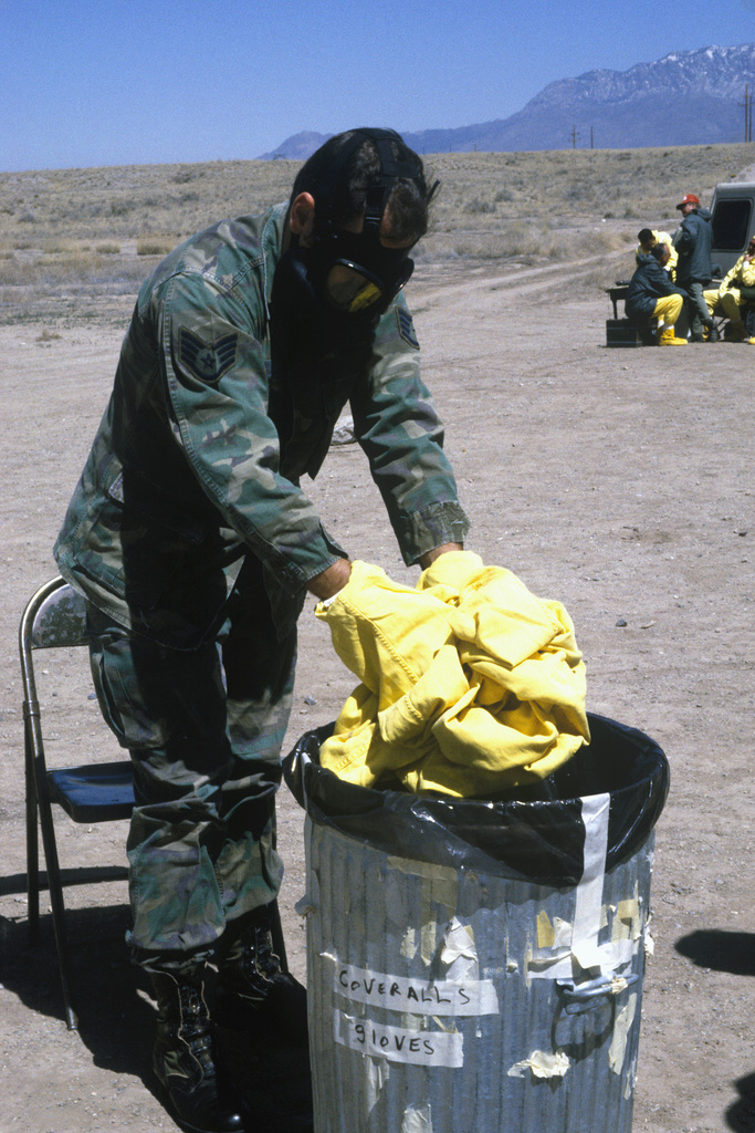 STAFF Sergeant Bruce Wojciechowski removes his nuclear biological chemical (NBC) protective suit as he processes through the contamination control station (CCS) during a Nuclear Emergency Team exercise at the Nuclear Weapons School. He is wearing an M-17 chemical-biological field mask