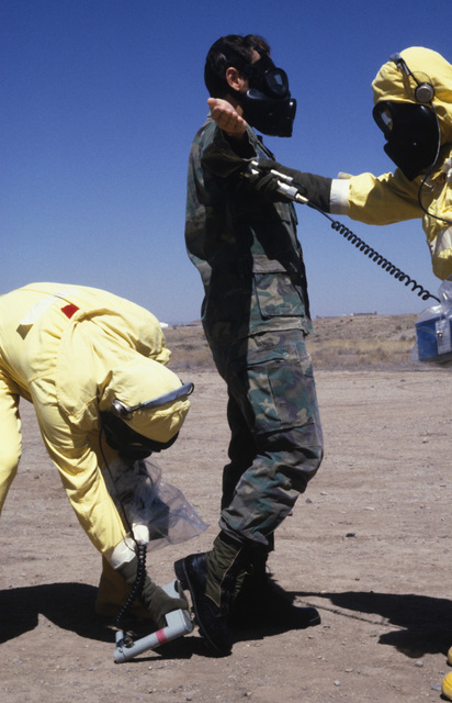 STAFF Sergeant (SSGT) Harold Heath and STAFF Sergeant (SSGT) James Holcomb, use monitoring devices to detect possible contamination on MASTER Sergeant James Kern, as he is processed through the contamination control station (CCS) during a Nuclear Emergency Team exercise at the Nuclear Weapons School. They are wearing NBC gear and M-17 chemical-biological field masks