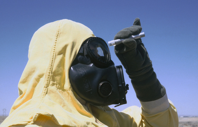 Technical Sergeant (TSGT) Jose Gonzalez, wearing nuclear-biological-chemical (NBC) protective gear, checks the calibration on a dosimeter as he participates in a Nuclear Emergency Team exercise at the Nuclear Weapons School. He is also wearing an M17 chemical-biological field mask