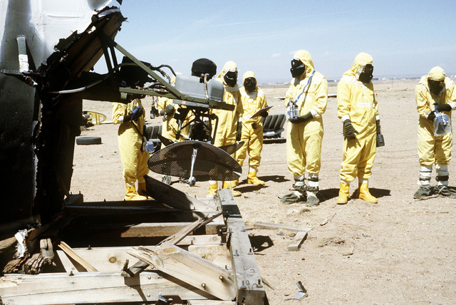 The Alpha team, wearing nuclear biological chemical (NBC) protective gear, uses monitoring equipment to detect possible contamination on an aircraft at a simulated crash site, during a Nuclear Emergency Team exercise at the Nuclear Weapons School