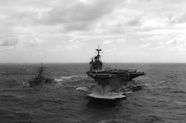 A bow view of the aircraft carrier USS SARATOGA (CV 60) underway in heavy seas while en route to the Mediterranean Sea. The guided missile frigate USS SAMUEL ELIOT MORISON (FFG 13) is off the carrier's starboard side
