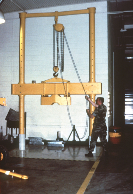 A member of the Aircraft Intermediate Maintenance Department (AIMD) Support Equipment section aligns chains on a load-tester pulley. The tester is used to check the stability of aircraft jacks