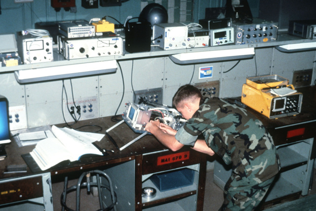 Private First Class of the Aircraft Intermediate Maintenance Department (AIMD) Precision Measuring Equipment (PME) section uses a variety of electronic diagnostic equipment to repair an AN/USM-425 oscillo-scope