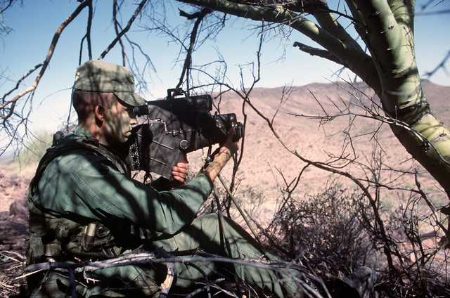 An Army Ranger sets up an AN/PAQ-1 laser target designator during Exercise QUICK FORCE 84-3. The laser projector will be used to assist A-7 Corsair II aircraft pilots as they drop laser guided bombs on designated targets