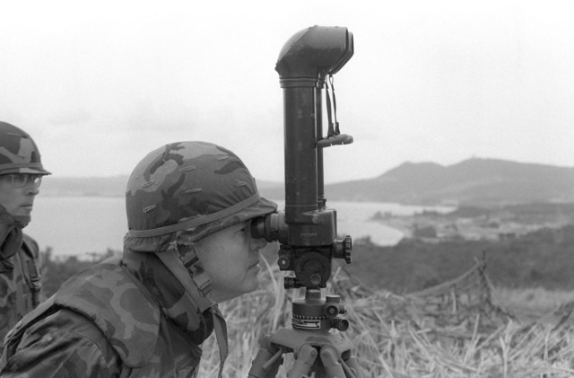 Lieutenant General D'Wayne Gray, cheif of staff, Headquarters Marine Corps, observes a live fire demonstration through an M-65 battery commander's telescope