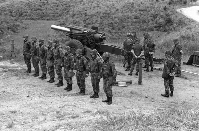 Marine artillerymen stand at attention prior to firing their M-114 155 mm howitzer during a live fire demonstration for Lieutenant General D'Wayne Gray, cheif of staff, Headquarters Marine Corps