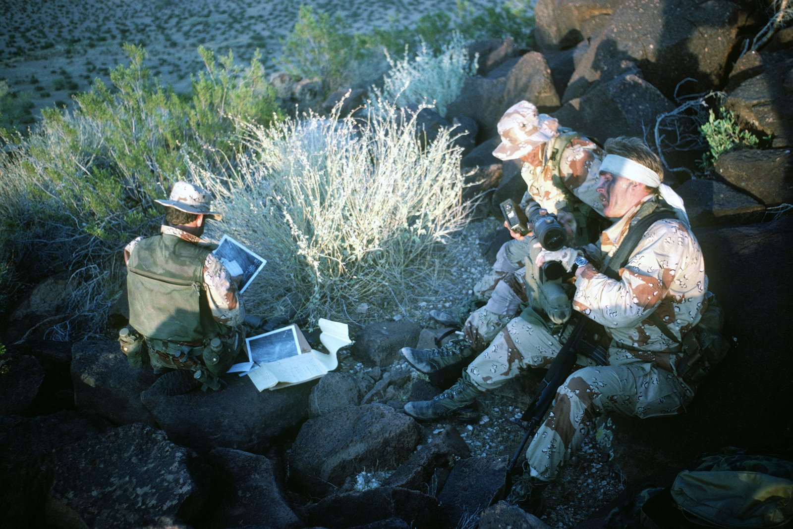Navy sea-air-land (SEAL) team members, wearing desert camouflage gear, prepare to use an AN/PAQ-1 laser target designator to assist A-7 Corsair II aircraft pilots as they drop laser guided bombs. The laser projector will help to distinguish the various targets for an accurate hit/kill ratio. The SEAL team members are participants of Exercise QUICK FORCE 84-3. The team member in the foreground holds an M16A1 rifle