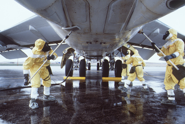 Ground crewmen, wearing nuclear-biological-chemical (NBC) clothing, perform decontamination procedures on a B-52 Stratofortress aircraft during Exercise GLOBAL SHIELD