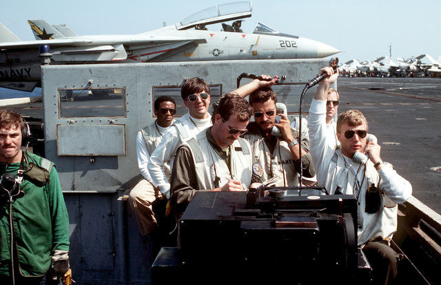 A landing signal officer and his assistant signal to aircraft carrier USS AMERICA (CV 66). In the background is an F-14A Tomcat aircraft. The AMERICA is participating in Exercise OCEAN VENTURE '84