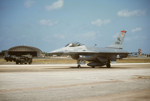A left front view of an F-16 Fighting Falcon aircraft on the runway during Operation OCEAN VENTURE '84. The aircraft is assigned to the 34th Tactical Fighter Squadron, 388th Tactical Fighter Wing. An M151 light utility vehicle is parked in the background