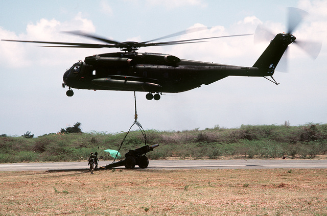 A Marine Corps CH-53E Super Stallion helicopter airlifts an M-114 155mm howitzer during Exercise Ocean Venture '84