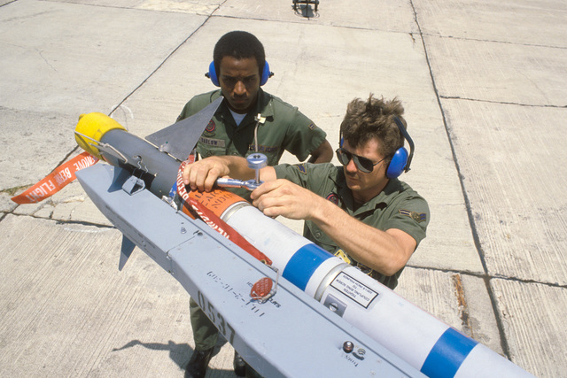AIRMAN First Class (A1C) Ray Barlon and A1C G. Thomas Jr., 388th Electronic Maintenance Squadron, check the torque on an AIM-9L Sidewinder missile during Operation OCEAN VENTURE '84