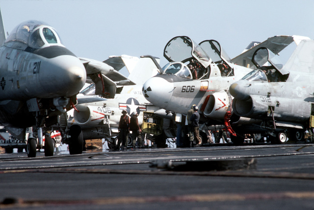 An EA-6B Prowler aircraft is parked (center) on the deck of the aircraft carrier USS AMERICA (CV 66). On the left is an F-14A Tomcat and on the right an A-7E Corsair II. The carrier is participating in Exercise OCEAN VENTURE '84