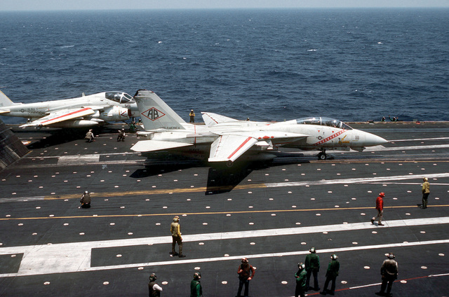 An F-14A Tomcat aircraft from Fighter Squadron 102 is ready to be launched from the aircraft carrier USS AMERICA (CV 66). In the background is a KA-6D Intruder tanker aircraft. The AMERICA is participating in Exercise OCEAN VENTURE '84