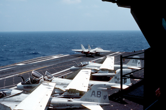An F-14A Tomcat aircraft is catapulted from the aircraft carrier USS AMERICA (CV 66). In the foreground are (front to back) an A-6E Intruder, an EA-6B Prowler and another A-6E. The AMERICA is participating in Exercise OCEAN VENTURE '84