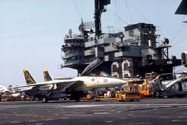 An F-14A Tomcat aircraft is towed by an MD-3A tow tractor aboard the aircraft carrier USS AMERICA (CV 66). The AMERICA is participating in Exercise OCEAN VENTURE '84