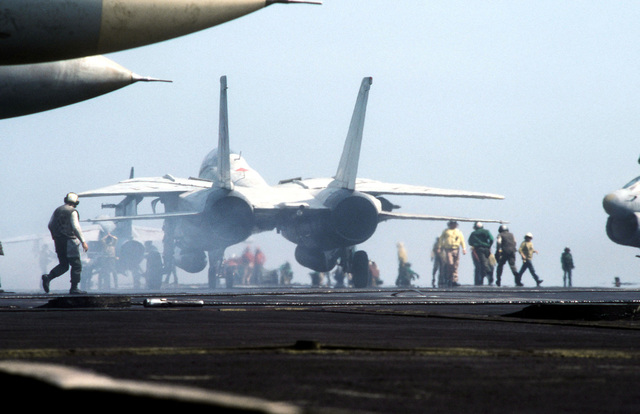 An F-14A Tomcat aircraft on the flight deck of the aircraft carrier USS AMERICA (CV 66). The AMERICA is participating in Exercise OCEAN VENTURE '84