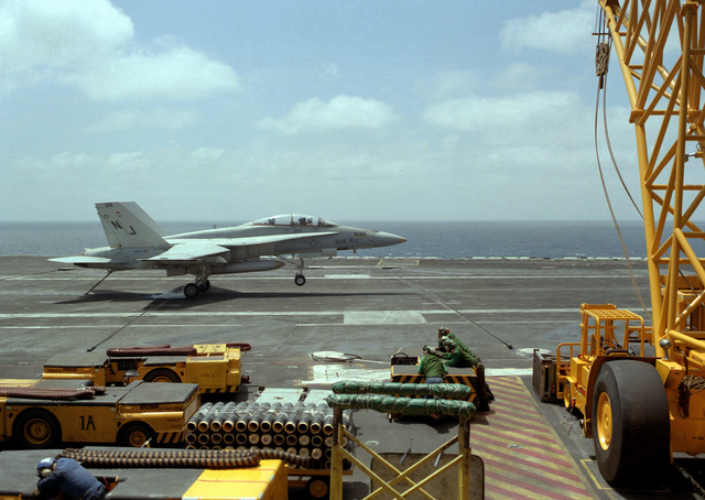 An F/A-18 Hornet aircraft from Fighter Attack Squadron 125 (VFA-125) touches down on the flight deck of the nuclear-powered aircraft carrier USS CARL VINSON (CVN-70) during flight operations. In the foreground are several MD-3A tow tractors and other types of aircraft handling equipment