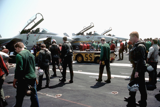 Crewmen search for foreign objects on the flight deck of the aircraft carrier USS AMERICA (CV 66) prior to flight operations during Exercise OCEAN VENTURE '84. In the background are three F-14A Tomcat aircraft and an MD-3A tow tractor