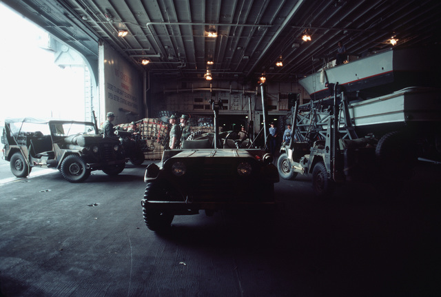 Marine Corps M151A1 light vehicles and other equipment inside the hangar bay of the amphibious assault ship USS IWO JIMA (LPH 2) during Exercise OCEAN VENTURE '84