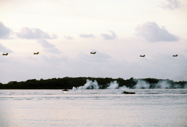Members of the 26th Marine Amphibious Unit conduct a beach assault on Vieques Island during Operation Ocean Venture '84 as five CH-46 Sea Knight helicopters fly over the beach